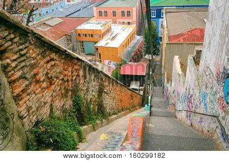 VALPARAISO CHILE - MAY 28: The funicular railway climbs past lively grafitti above brightly-colored houses in Valparaiso Chile on May 28 2014