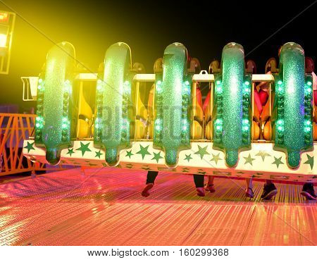 Rear view of amusement park ride with people waiting for the start of the machine light flare