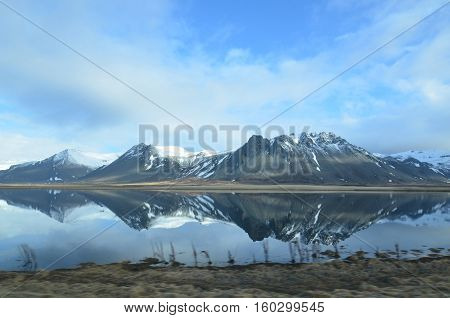 Beautifu snow covered mountains in Iceland reflecting in a pool of water.