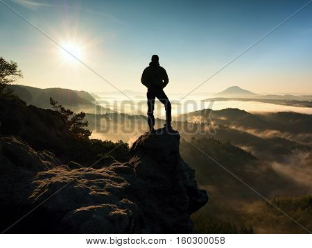 Man On Top Of Mountain. Hiker Climbed On Peak Of Rock Above Foggy Valley.