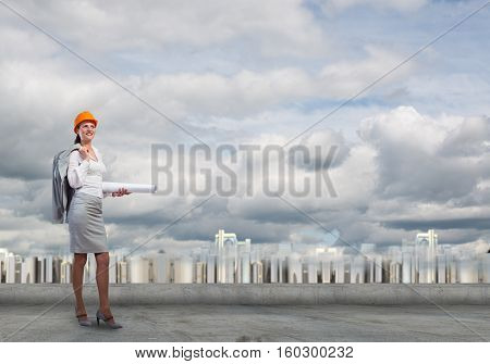 Young woman architect in hardhat holding project in hand