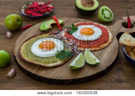 Huevos divorciados, delicious food with eggs, fresh salad and herbs and spicy and herby sauce, close view
