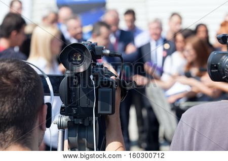 Filming an media event with a video camera. Press conference. TV broadcasting.