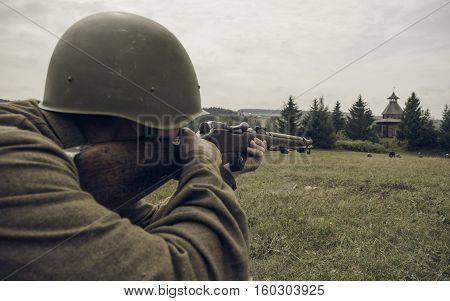 PERM RUSSIA - JULY 30 2016: Historical reenactment of World War II summer 1942. Soviet soldier aiming a rifle