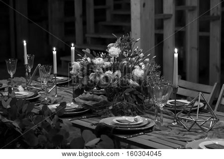 Decoration wedding table before a banquet in a wooden barn. Candles bouquet stemware. Black and white.