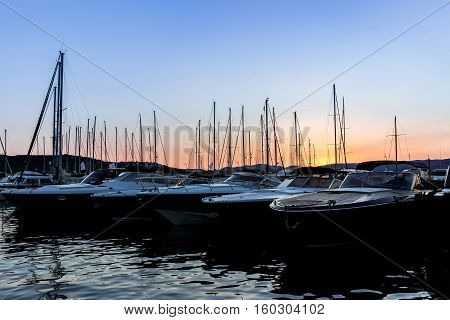 boats in dock with orange sunshine at sunset