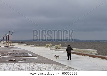 An unidentified man and his dog going through the icy deserted embankment on a cloudy winter day