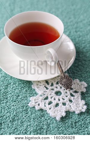 Winter drink: Flavored black tea in white porcelain cup and crocheted snowflake