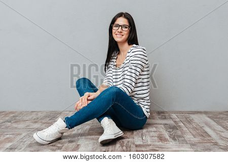 Photo of happy young woman wearing eyeglasses sitting on floor over grey background. Look at camera.