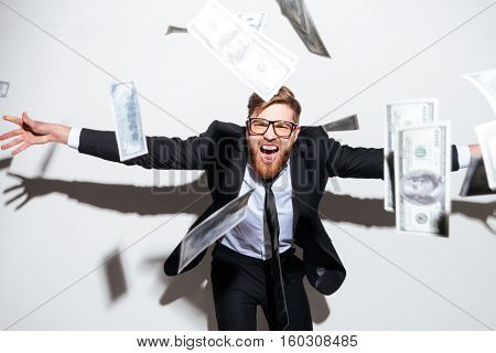 Bearded Business man in suit and glasses with falling money and arms outstretched to the sides. Isolated gray background