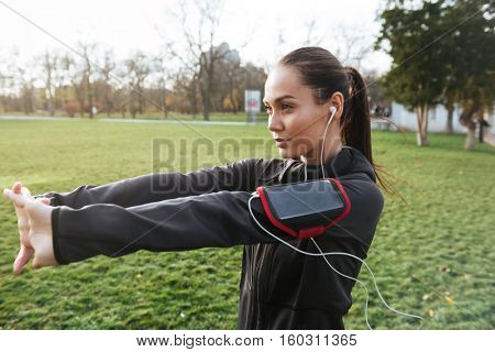 Female runner warming up in warm clothes in autumn park. Side view.