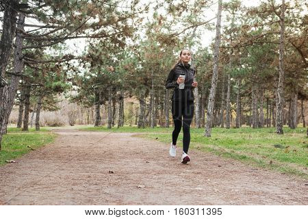 Full length image of Woman running in warm clothes in autumn park with cup of water.