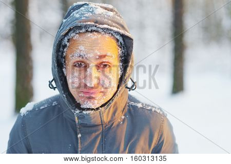 Frozen young man in a jacket with a hood covered with snow in winter forest. Snowflakes lie on the eyelashes eyebrows cheeks.