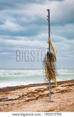 Coiled net for volleyball on the mast. Sandy ocean beach. Hurricane. Cuba. Varadero.