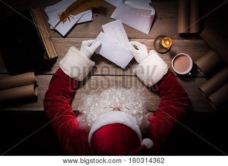 Santa Claus sitting at his room and reading Christmas letter