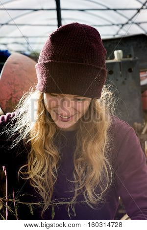 Smiling Blonde Woman In Maroon Hat In Rural Setting
