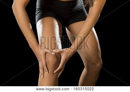cropped close up view young sport woman holding injured knee suffering pain in ligaments injury or pulled muscle isolated on black background in fitness accident and body health care