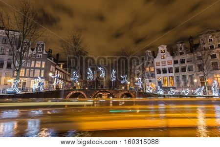 AMSTERDAM - DEC 29, 2015: Tour boats leave light trails in front of the artwork