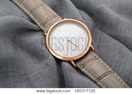 Gray band wrist watch on gray silk fabric background