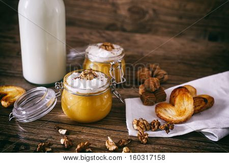 Pumpkin milkshake with whipped cream, toffee, walnut and honey cookies. Bottle of milk. Dark wooden background, selective focus.