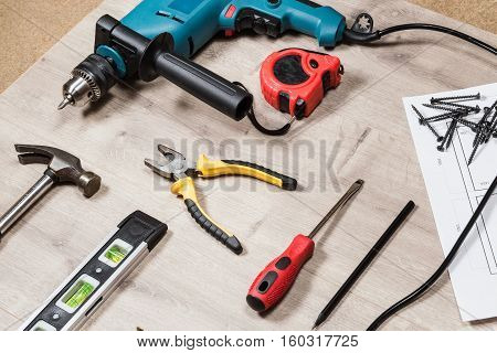 Set of construction tools to repair on a wooden surface: drill, hammer, pliers, self-tapping screws, roulette, construction level, drawing, construction pencil. Side view