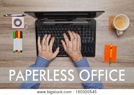 Male hand typing on laptop, message PAPERLESS OFFICE