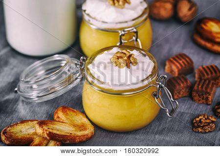 Pumpkin milkshake with whipped cream, toffee, walnut and honey cookies. Bottle of milk. Dark wooden background, selective focus.