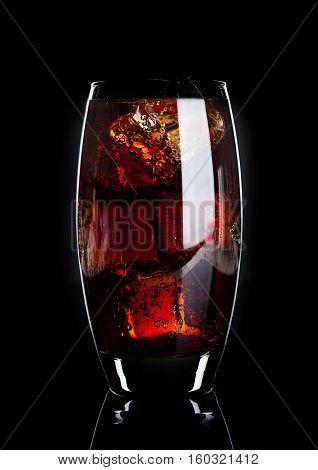 Glass of cold cola soda drink with ice cubes on black background