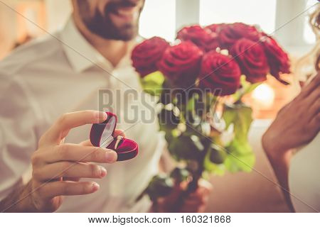Handsome elegant guy is proposing to his beautiful girlfriend giving her roses and smiling while they having a romantic date at home