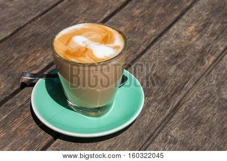 isolated caffe latte in glass on wooden table with copy space