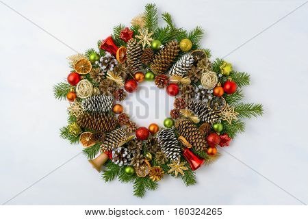 Christmas wreath with pine cones red and golden ornaments. Christmas background with baubles jingle bells and dried orange slices.