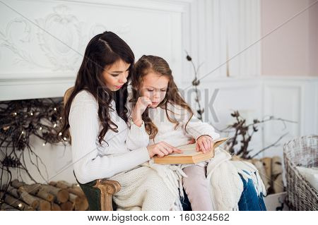 Merry Christmas and Happy Holidays, Pretty young mom reading a book to her cute daughter near tree indoors