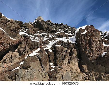 A fresh coat of snow on jagged lava rocks in Central Oregon on a sunny winter morning.