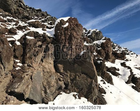 Jagged lava rock boulders with a fresh coat of snow and a sunny blue sky on a Central Oregon morning.