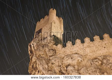 Star trails and medieval castle in ancient village of Frias Burgos Spain.