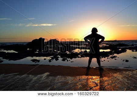 Sihouette of a teenage boy facing the ocean at sunset
