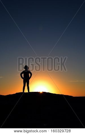 silhouette of child standing on a hill facing the sun