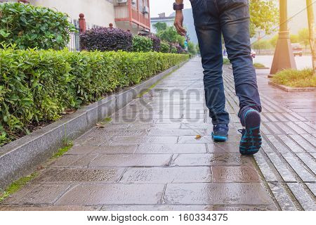 Man Jeans And Sneaker Shoes Walking On Footpath