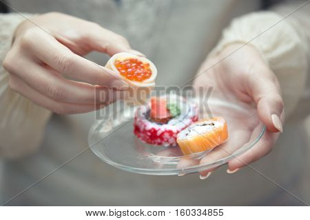 Human hands holding plate with sushi. Close-up view