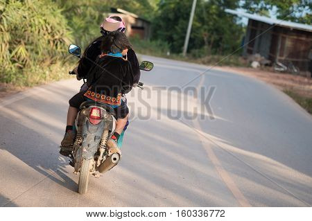 Hmong hill tribe young woman riding motorbike in Hmong village on mountain in Nan province, Thailand.