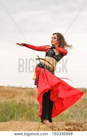 Oriental Beauty dance with a sword. Tribal style. Lovely girl in costume dancing outdoors. Nomads. Passionate dance.