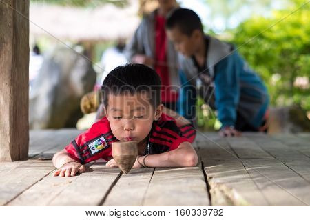 Hmong tribal young children enjoying wood spinning traditional game in village park