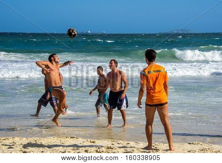 6 December 2016. Three brazilian men playing beach football in motion on the background of waves of Atlantic ocean at Copacabana beach, Rio de Janeiro, Brazil