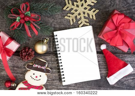 Christmas background decorations with wrap gift box and red bibbon bow snowman cookie santa claus hat gold snowflake and blank open notebook with copy space on rustic wooden table from above Christmas planning concept