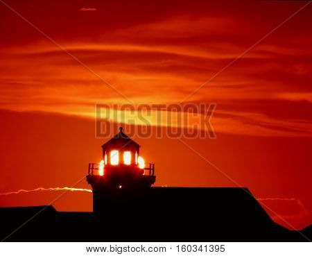 Like a guiding light of hope in the darkness, the light from the setting sun is refracted from this old lighthouse tower to send up brilliant illumination.