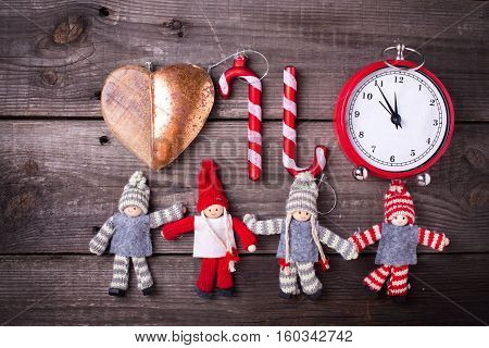 Christmas background. Clock candy canes and decorative dollies on aged wooden background. Flat lay.