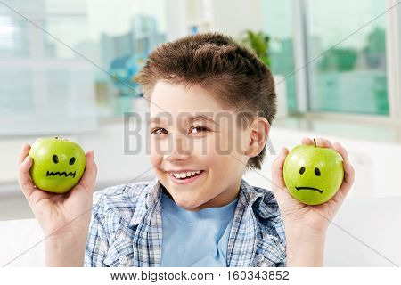 Portrait of happy little boy holding green apples