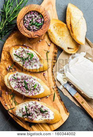 Toasted bread bruschetta with cream cheese and garlic edible flowers on olive wooden cutting board on stone slate gray background. Top view