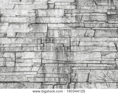 Closeup surface brick pattern at old and dirty wet stone brick wall textured background in black and white tone