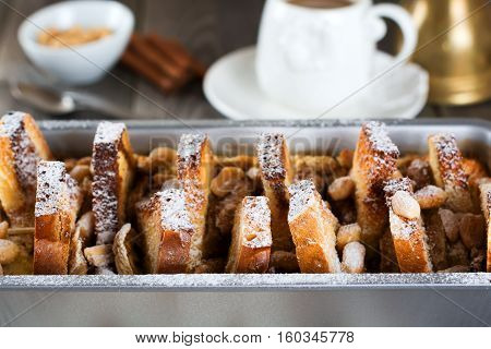 Baked toast with bananas and peanuts on the old wooden background. Rustic style. Selective focus.